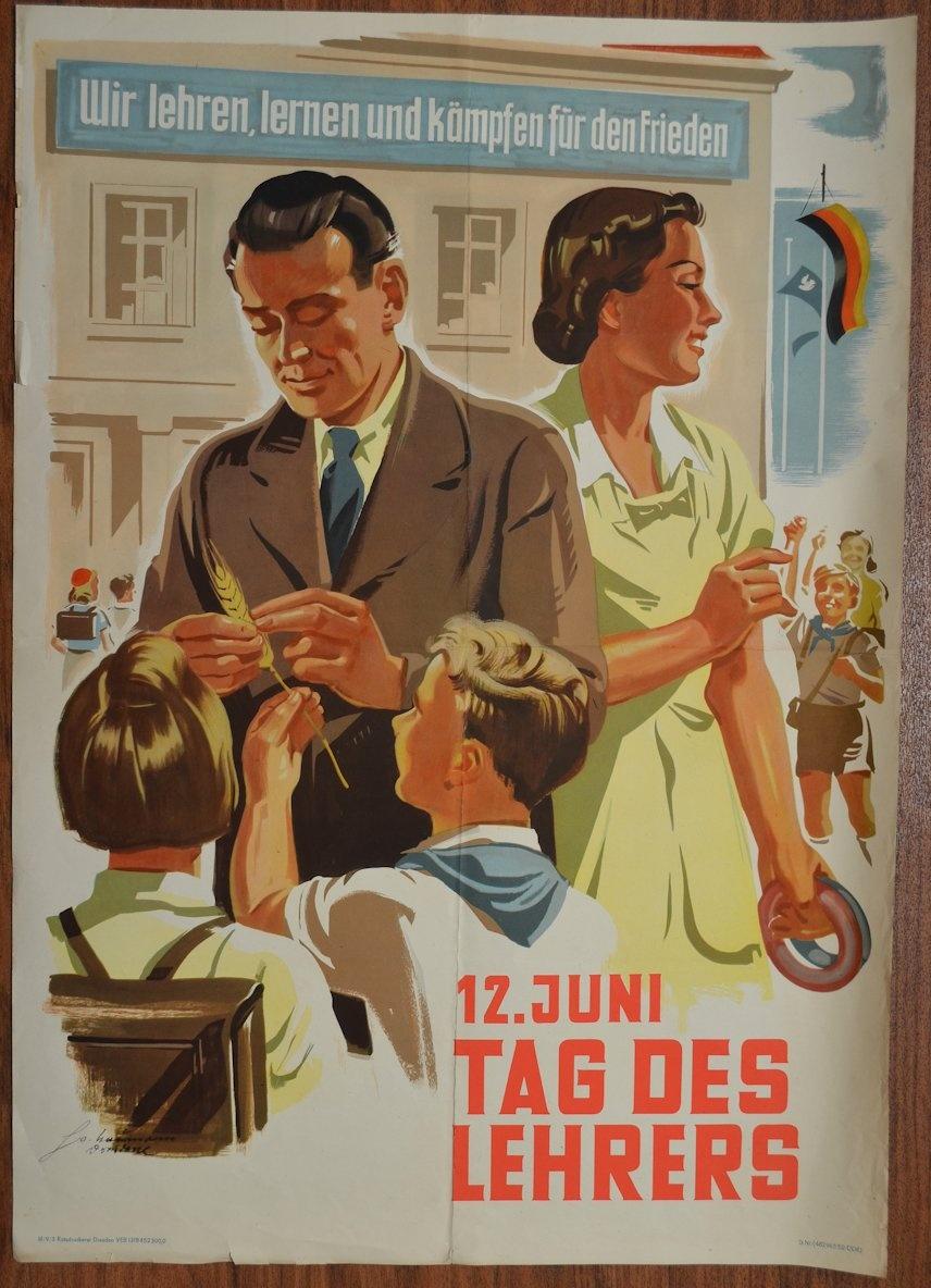 """Gesamtansicht ----- Das Plakat zeigt im Vordergrund die Zeichnung eines Lehrers und einer Lehrerin. Der Lehrer betrachtet mit 2 Schülern eine Ähre. Die Lehrerin hat in der linken Hand 2 Ringe und schaut nach Schülern die sie grüßen. Im Hintergrund ist das Schulgebäude, in welches gerade Schüler laufen. Am oberen Rand findet sich der Schriftzug """"Wir lehren, lernen und kämpfen für den Frieden"""" Die Urheberrecht liegen bei Horst Uwe Naumann."""